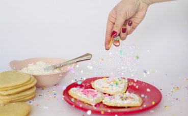 Hand putting sprinkles on cookies