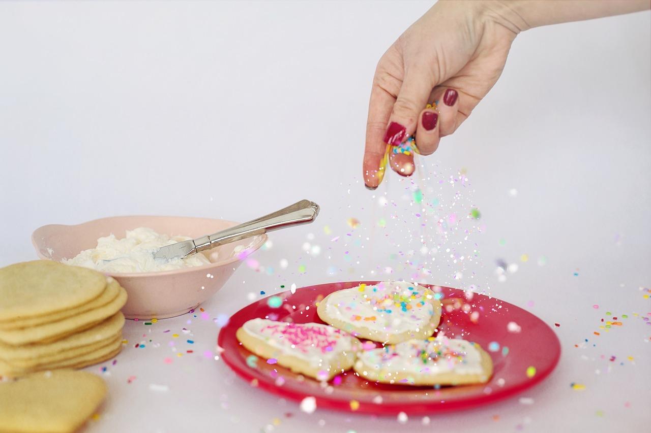 Hand putting sprinkles on cookies